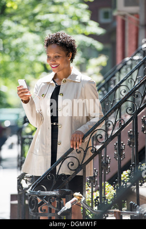City. A woman on steps outside a town house, checking her smart phone. - Stock Photo