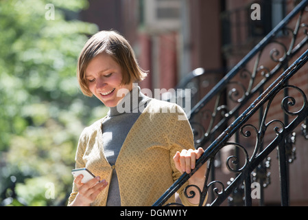 City. A woman on steps outside a townhouse, checking her smart phone. - Stock Photo