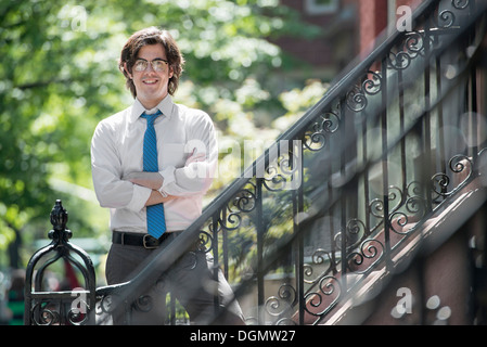 City. A young man in w white shirt and blue tie, standing with arms folded outside a townhouse, on the steps. - Stock Photo