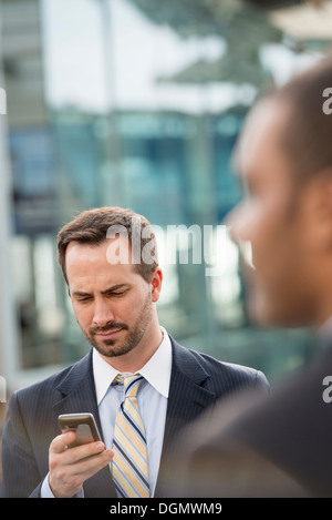 City. A man in a business suit checking his messages on his smart phone. - Stock Photo