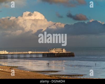 Evening light on the west side of Worthing pier reflected in a clam sea with strong clouds to the horizon England - Stock Photo