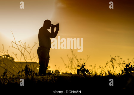 Silhouette of a standing photographer in a landscape at sunset - Stock Photo