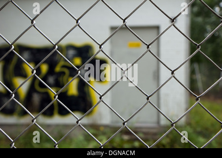 Illegal graffiti behind a fence, focused on the fence - Stock Photo