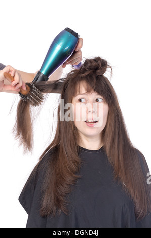 Woman enjoying having her hair blow dried, isolated on white - Stock Photo