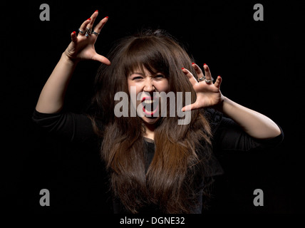 Woman throwing a temper tantrum screaming in anger and clawing the air with her hands on a dark background - Stock Photo