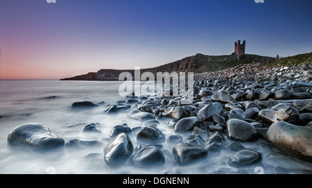 Pebbly beach with castle ruins in the background - Stock Photo