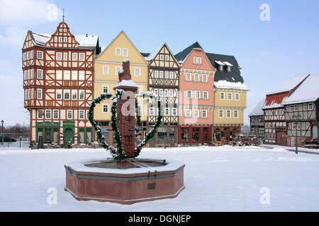 Historic row of houses on market square, market well, snow, winter in Hessenpark, Neu-Anspach, Taunus, Hesse - Stock Photo