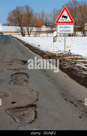Warning sign, road damage, potholes in an asphalt road caused by frost damage in the cold winter 2009-2010 - Stock Photo