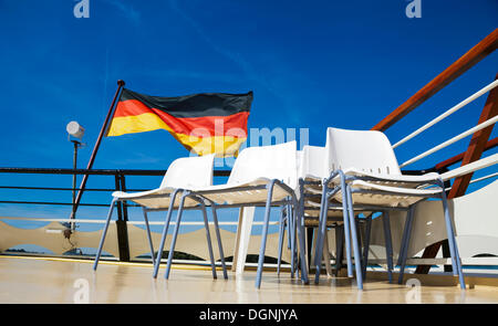 German flag flying behind empty rows of chairs on the rear of an excursion boat, Berlin - Stock Photo