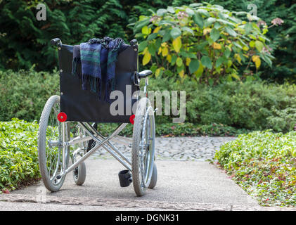Abandoned wheelchair in a green area, Berlin, Germany - Stock Photo
