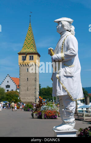 Street performer, living statue in front of the Mangturm tower at the harbor, Lindau, Lake Constance, Bavaria - Stock Photo