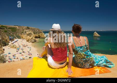 Two women on the beach, Praia Dona Ana in Lagos, Algarve, Portugal, Europe - Stock Photo