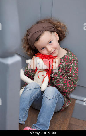 Red-haired girl, 5 years old, sitting on a staircase with a doll - Stock Photo