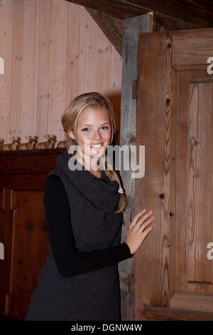 Smiling young woman leaning against an old door - Stock Photo