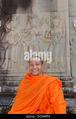 Buddhist monk in the centre of Angkor Wat sitting in front of a relief depicting Apsara from Hindu mythology, Cambodia - Stock Photo