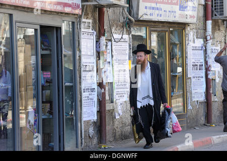 Street scene with an Orthodox Jew in the Me'a She'arim district, with typical houses and wall newspapers, Jerusalem, - Stock Photo