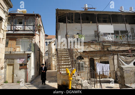 Ultra-Orthodox Jew with typical houses in the district of Me'a She'arim or Mea Shearim, Jerusalem, Israel, Middle - Stock Photo