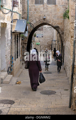 Palestinian woman wearing a headscarf and students walking on an alley in the Arab district, Jerusalem, Israel, - Stock Photo
