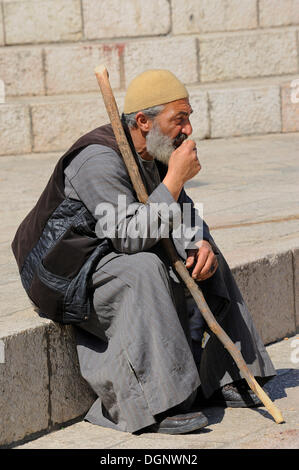 Palestinian man sitting on the steps outside the Damascus Gate in front of the Old City, Jerusalem, Israel, Middle - Stock Photo
