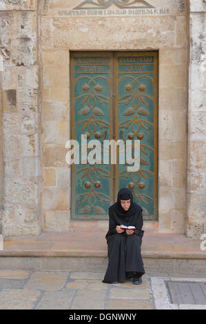 Russian Orthodox nun praying in front of the door of the Church of the Holy Sepulchre, Christian Quarter in the - Stock Photo