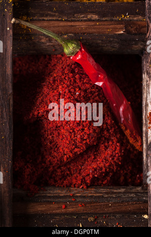 Top view on red hot chili pepper and ground paprika in old wooden box - Stock Photo