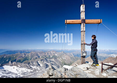 Mountain climber at the summit cross of Hochfeiler Mountain, looking over the valleys of Pfitschertal and Wipptal, - Stock Photo