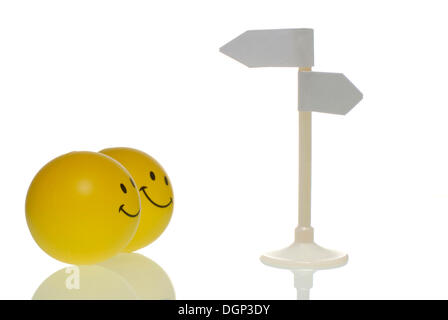 Two smileys looking at a blank direction sign, symbolic image for direction, decision - Stock Photo