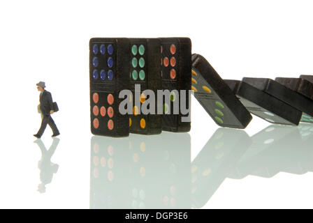 Dominoes falling on a business man figurine, symbolic image for crisis catching up with manager - Stock Photo
