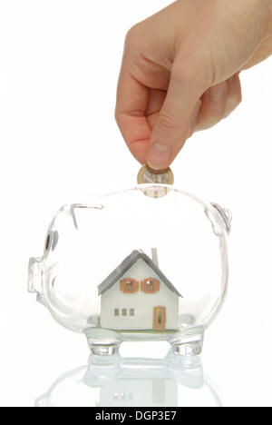 Hand putting coin into piggy bank with a house, symbolic image for building society savings - Stock Photo