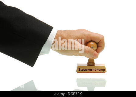 Manager hand holding a stamp labelled Steuererhoehung, German for tax increase - Stock Photo