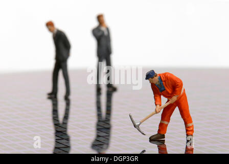 A construction worker and two businessmen figurines standing on a silicon wafer, electronic component, semiconductor - Stock Photo