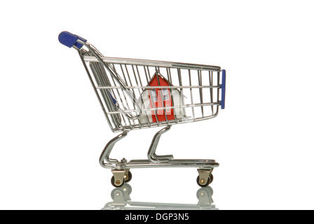 Small house in a shopping cart, symbolic image for property purchases in discount stores - Stock Photo