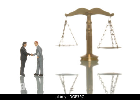 Miniature businessmen figures shaking hands in front of a balanced scale, symbolic image for balanced business - Stock Photo