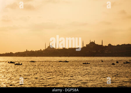 Fishing Boats on the Sea of Marmara in front of the silhouettes of the Blue Mosque and Hagia Sophia, Istanbul, Turkey - Stock Photo