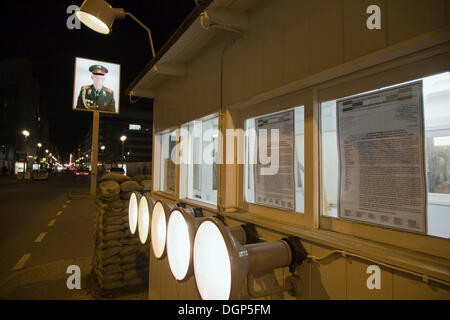 Former border crossing at Checkpoint Charlie with a portrait of a Soviet soldier, Berlin - Stock Photo