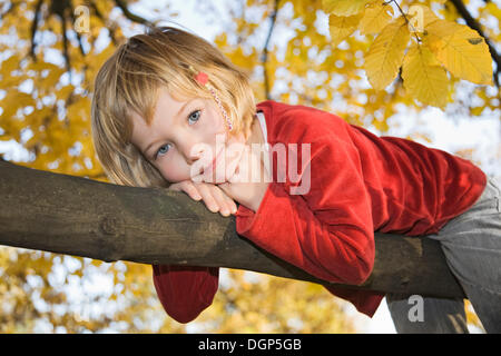 Little girl on a branch - Stock Photo
