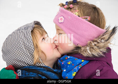 Two sisters kissing - Stock Photo