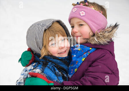 Two sisters hugging each other - Stock Photo