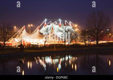 Christmas circus at the Cannstatter Wasen festival area reflected in the Neckar River, Stuttgart, Baden-Wuerttemberg - Stock Photo
