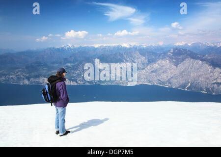 Hiker enjoying the view from Monte Baldo on Lake Garda and the Alps, Lake Garda, Lombardy, Italy, Europe - Stock Photo