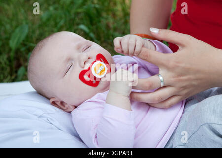 A few months old baby clinging to the fingers of its mother - Stock Photo