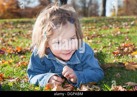 Girl, 4, in a park in autumn - Stock Photo