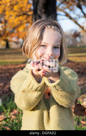 Six-year-old girl offering chestnuts - Stock Photo