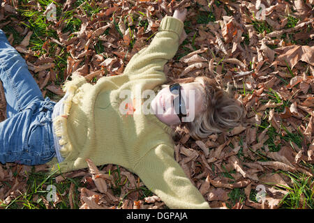 Six-year-old girl playing in the autumn leaves - Stock Photo