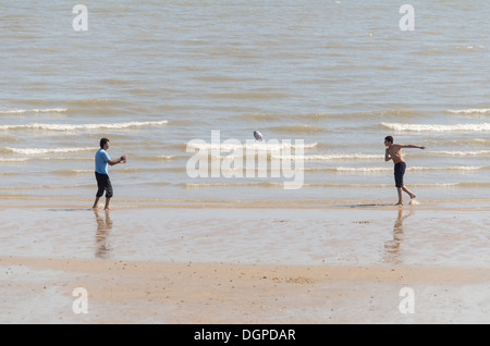 Throwing a rugby ball on the beach - Stock Photo