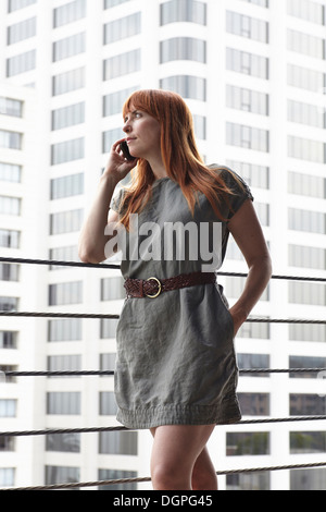 Mid adult woman using mobile phone in city - Stock Photo