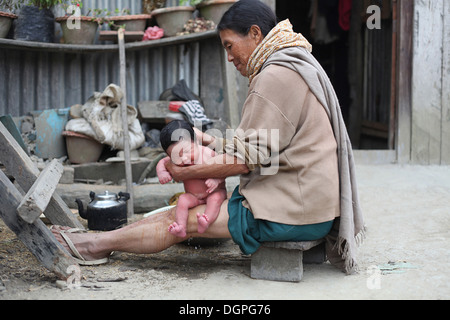 New born baby being bathed, Mimo village, Nagaland, India. - Stock Photo