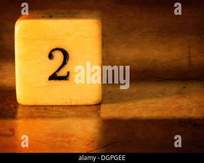 A dice displaying the number 2 whilst resting on a wooden gaming board - Stock Photo