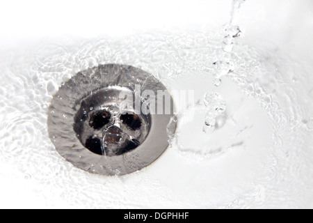 Water Wasting in a Bathroom Sink - Stock Photo