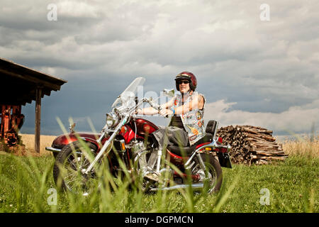 Man with a prosthetic leg riding a motorbike with a side car, chopper - Stock Photo